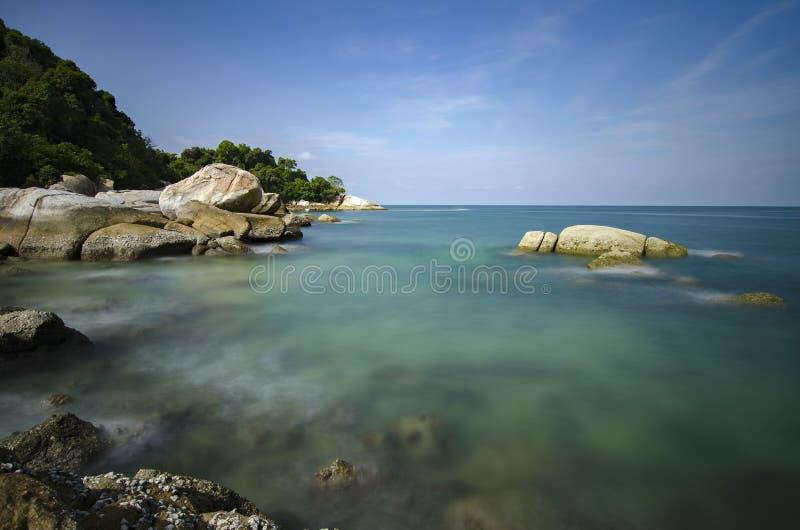 Dzika tropikalna wyspa i skalisty denny brzeg pod jaskrawym słonecznym dniem i niebieskim niebem obrazy royalty free
