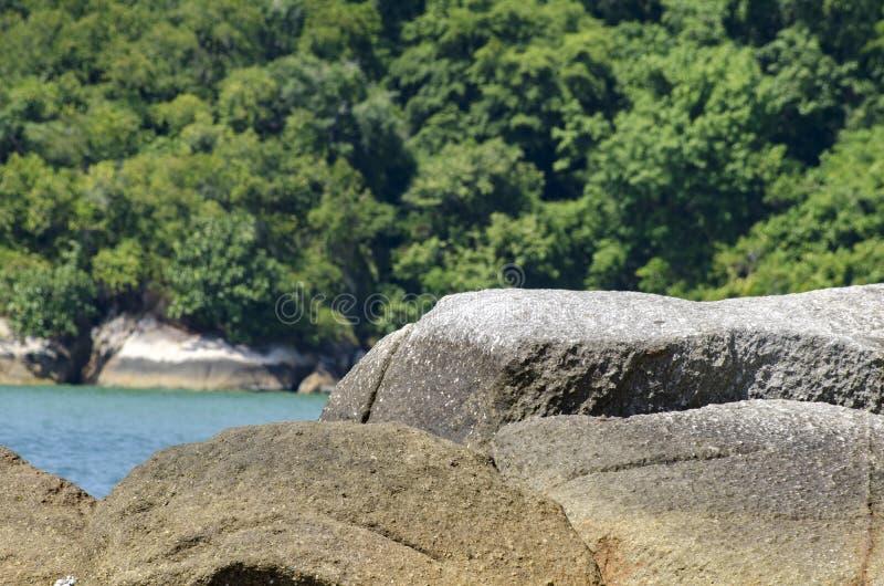 Dzika tropikalna wyspa i skalisty denny brzeg pod jaskrawym słonecznym dniem i niebieskim niebem fotografia royalty free