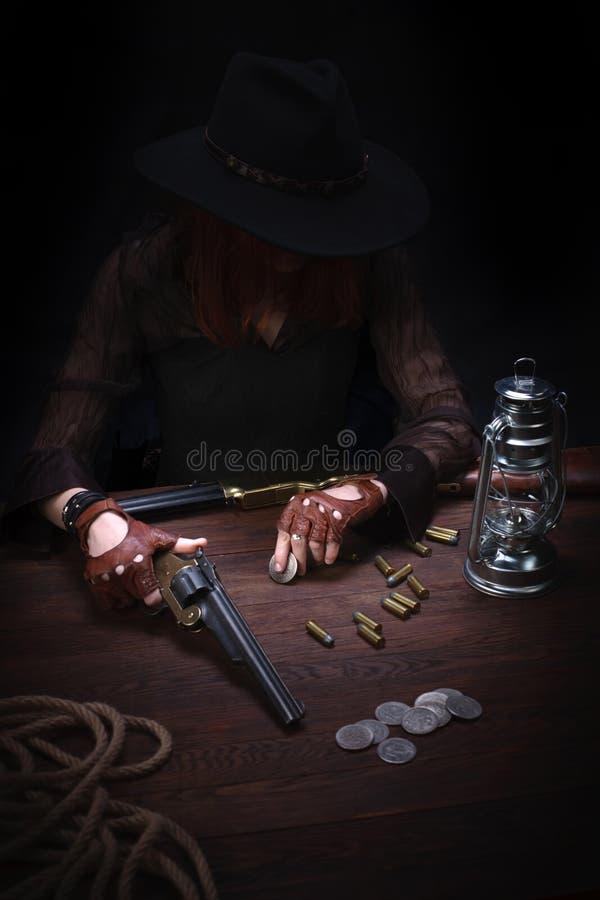 dzika zachodnia dziewczyna z kolta pistoletu obsiadaniem przy sto?em z amunicyjnymi i srebnymi monetami fotografia stock