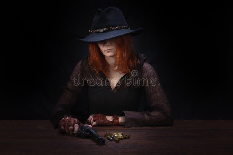 dzika zachodnia dziewczyna z kolta pistoletu obsiadaniem przy sto?em z amunicyjnymi i srebnymi monetami zdjęcie stock