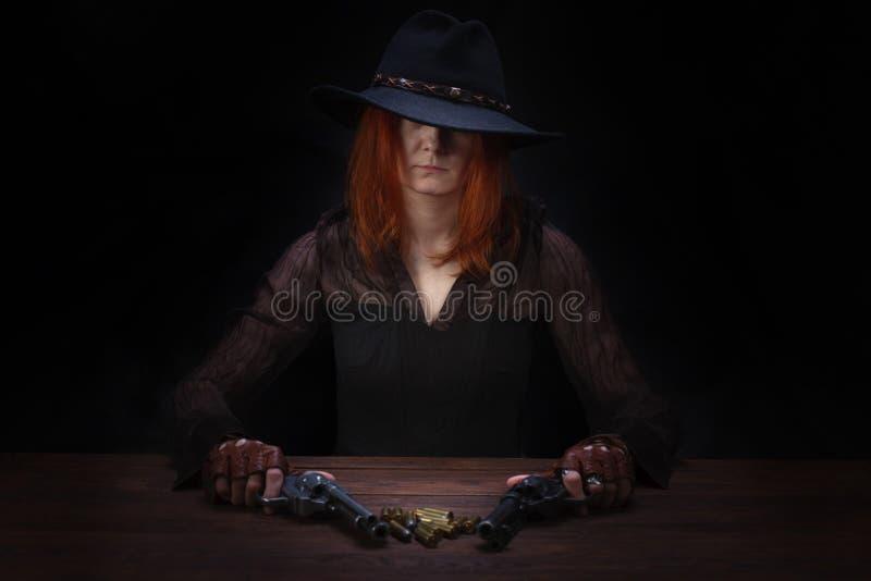 dzika zachodnia dziewczyna z kolta pistoletu obsiadaniem przy sto?em z amunicyjnymi i srebnymi monetami obraz stock