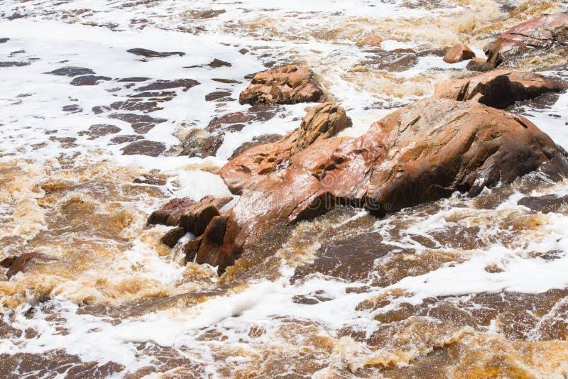 Dziki biel zalewał rzeczny działający szorstkiego wokoło skał zdjęcia stock