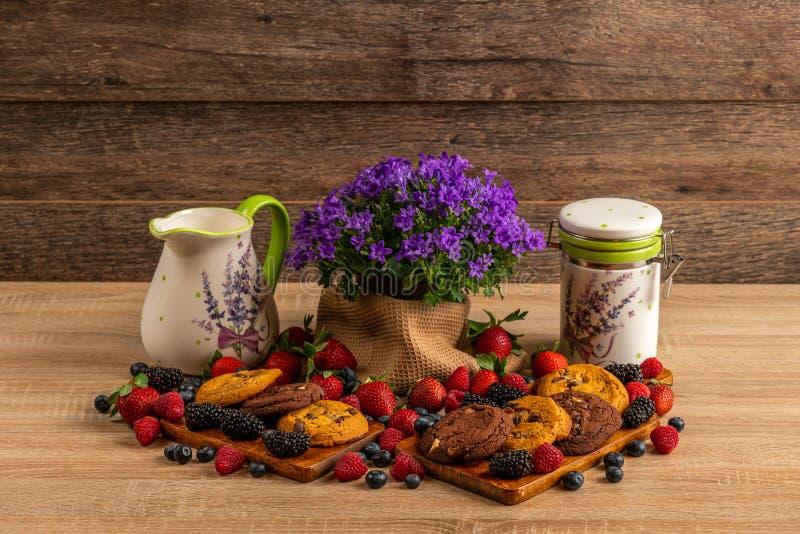 Dzikie jagody, czekoladowi ciastka z kampanulą i ceramiczny dzbanek, fotografia stock