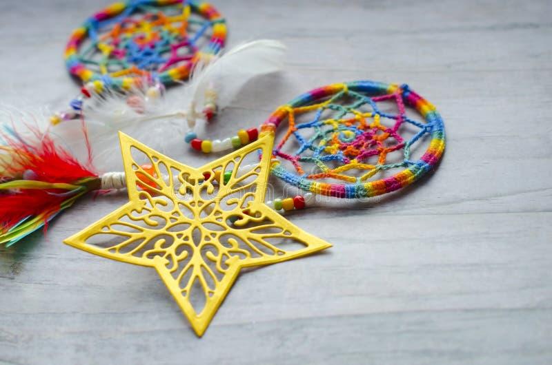 Dziurkowata openwork złota gwiazda na szarym drewnianym tle Dreamcatcher z piórkami z barwionymi koralikami fotografia royalty free