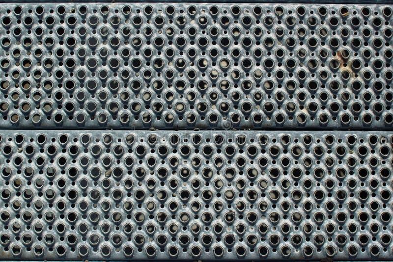 Dziurkowaty metal kroczy zbliżenie jako przemysłowy tło obrazy stock