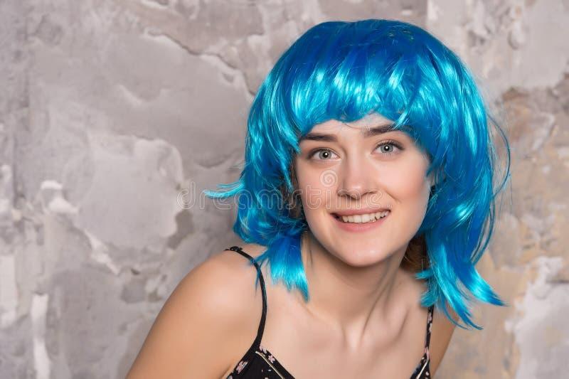 Dziwaczny pojęcie Dama na uśmiechniętej twarzy pozuje w błękitnej peruce, betonowej ściany tło Kobieta z błękitnym włosy patrzeje obrazy stock