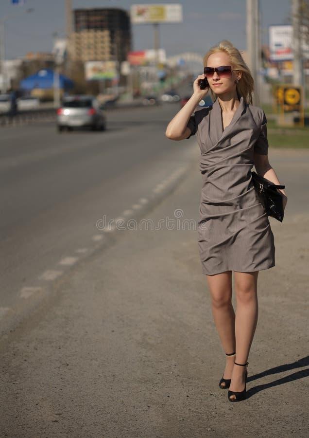 dzwoniący smokingowego popielatego telefon chodząca kobieta zdjęcia stock