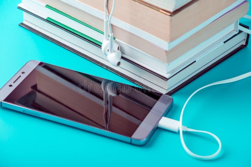 Dzwoni z białymi słuchawkami obok sterty książki na błękitnym tle Pojęcie audiobooks i nowożytna edukacja obraz stock