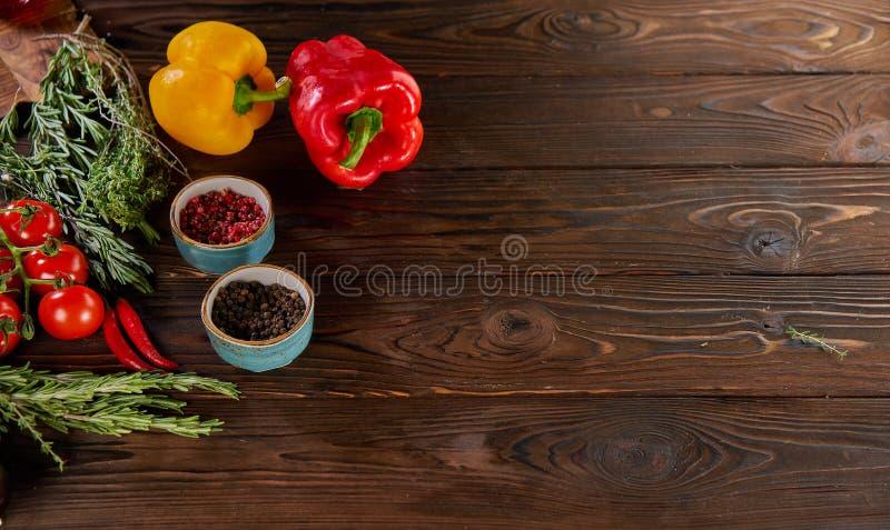 Dzwonkowi pieprze, rozmaryny, czereśniowi pomidory i inni składniki dla gotować na drewnianego nieociosanego tła odgórnym widoku, zdjęcia stock