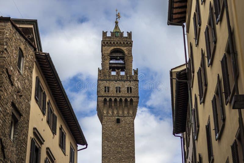 Dzwonkowy wierza punkt zwrotny między dwa starymi Włoskimi fasadami buduje w Firenze, Włochy obrazy stock