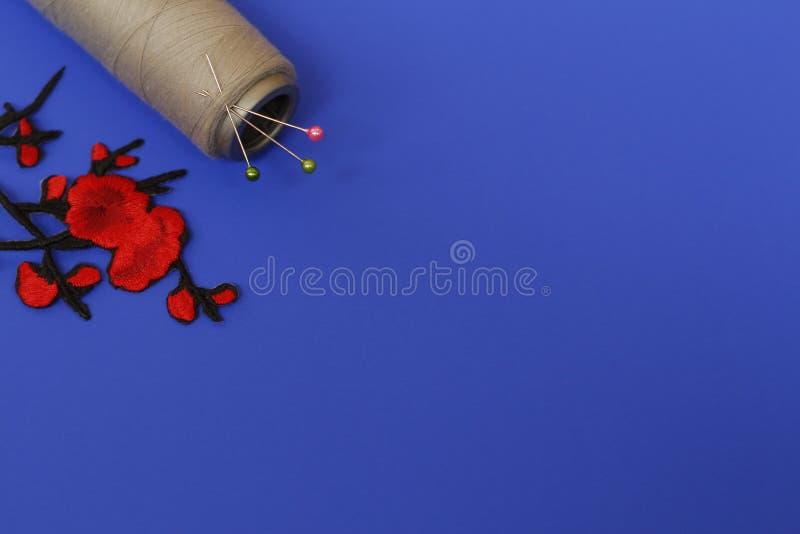 Eén grote spoel met draad en naalden op een blauwe achtergrond royalty-vrije stock foto