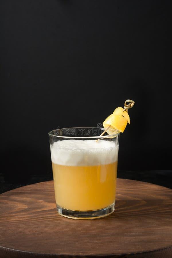 Eén shot whiskey zure cocktail - bourbon met citroensap, suikerstroop en eiwit in glas Verticale oriëntatie stock fotografie