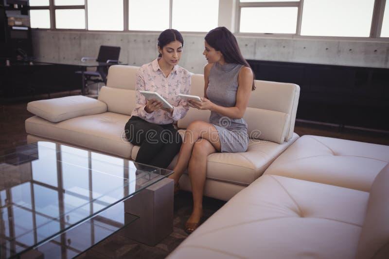 Żeńscy bizneswomany dyskutuje nad cyfrową pastylką podczas gdy siedzący na kanapie obrazy stock
