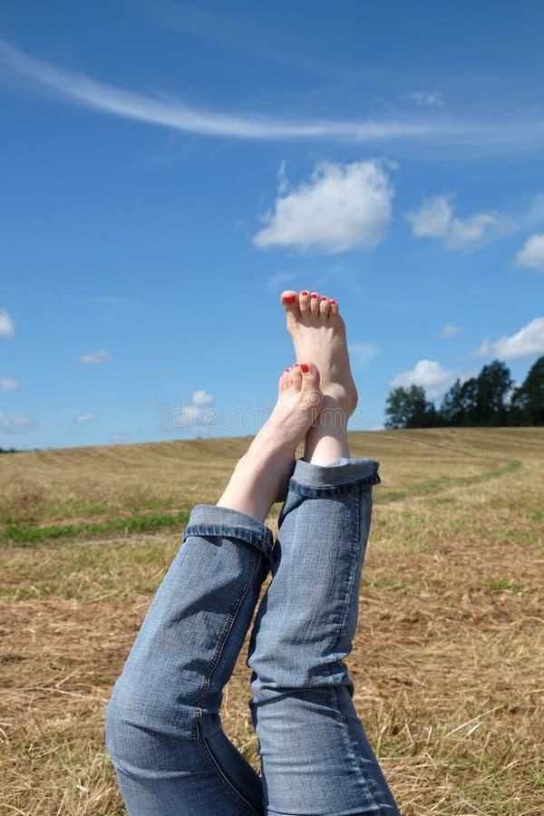 Żeńscy nadzy cieki z czerwonymi gwoździami przeciw lato krajobrazowi obrazy stock