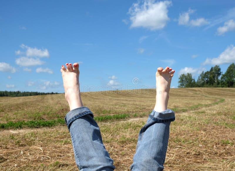 Żeńscy nadzy cieki z czerwonymi gwoździami przeciw lato krajobrazowi zdjęcia stock