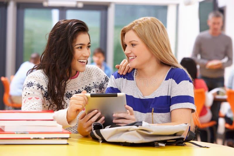 Żeńscy Nastoletni ucznie W sala lekcyjnej Z Cyfrowej pastylką zdjęcia stock