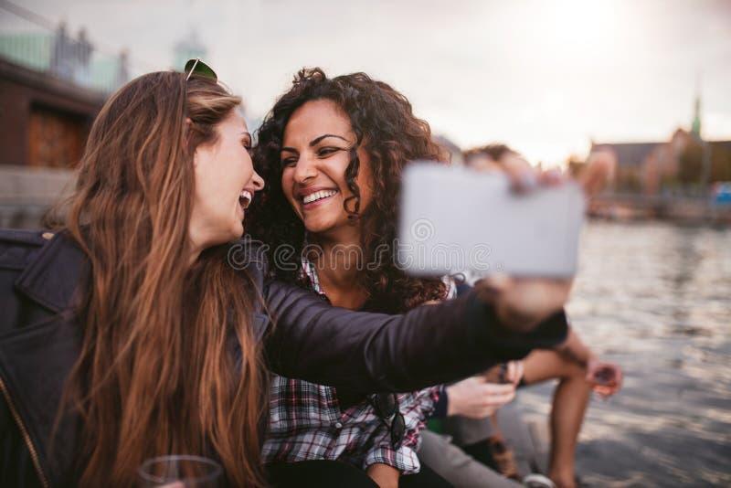 Żeńscy przyjaciele bierze selfie jeziorem zdjęcia stock