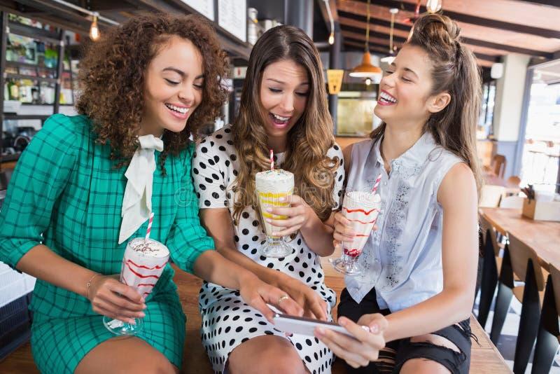 Żeńscy przyjaciele dyskutuje nad telefonem komórkowym podczas gdy siedzący w restauraci obrazy stock