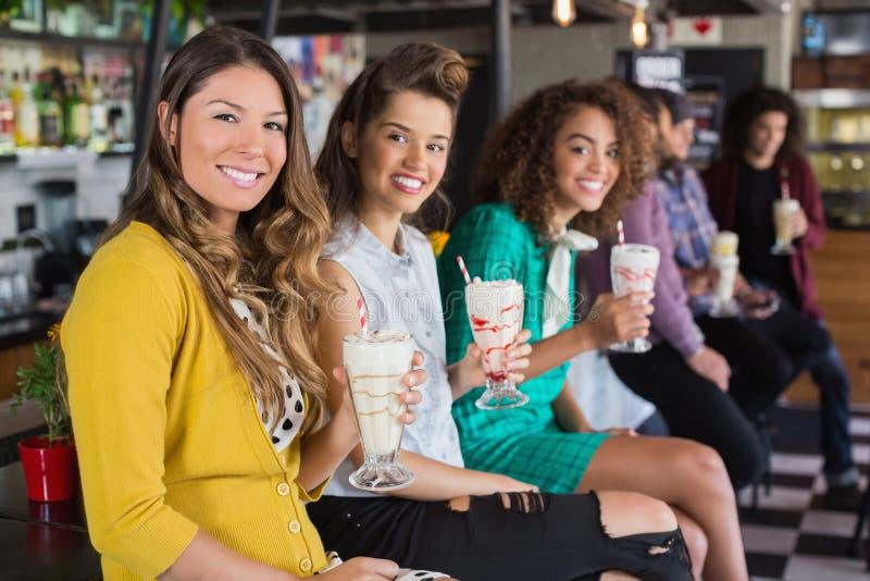 Żeńscy przyjaciele pije smoothie przy restauracją obrazy royalty free