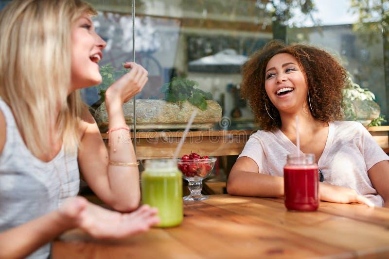 Żeńscy przyjaciele przy outdoors kawiarnią ma zabawę fotografia royalty free