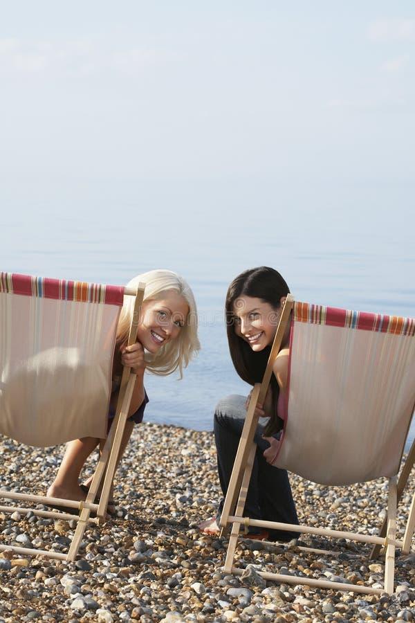 Żeńscy przyjaciele Siedzi Na Deckchairs Przy plażą obrazy royalty free