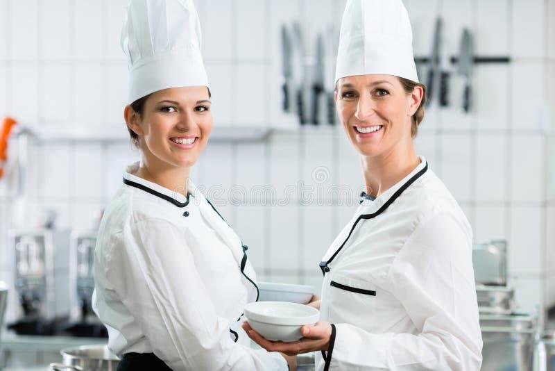 Żeńscy szefowie kuchni jest ubranym biel w handlowej kuchni mundurują obraz royalty free