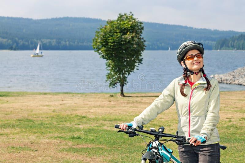 Żeńscy turystyczni cyklistów stojaki na brzeg jezioro na tle o obrazy stock
