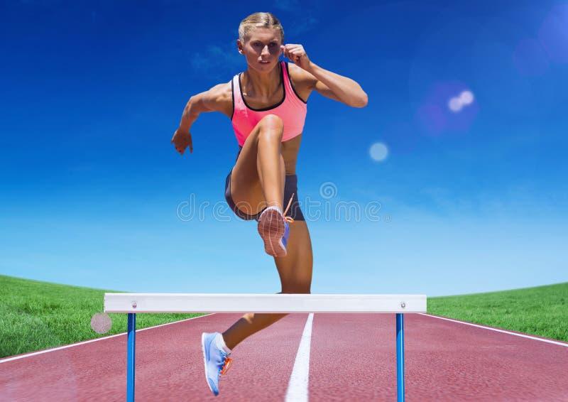 Żeńska atleta skacze nad przeszkodą na biegowym śladzie zdjęcia stock