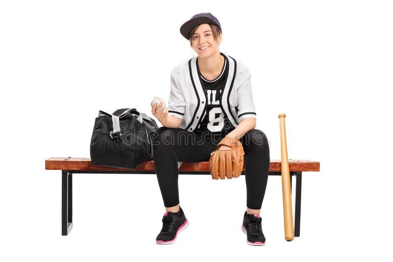 Żeńska atleta trzyma baseballa sadzający na ławce fotografia stock