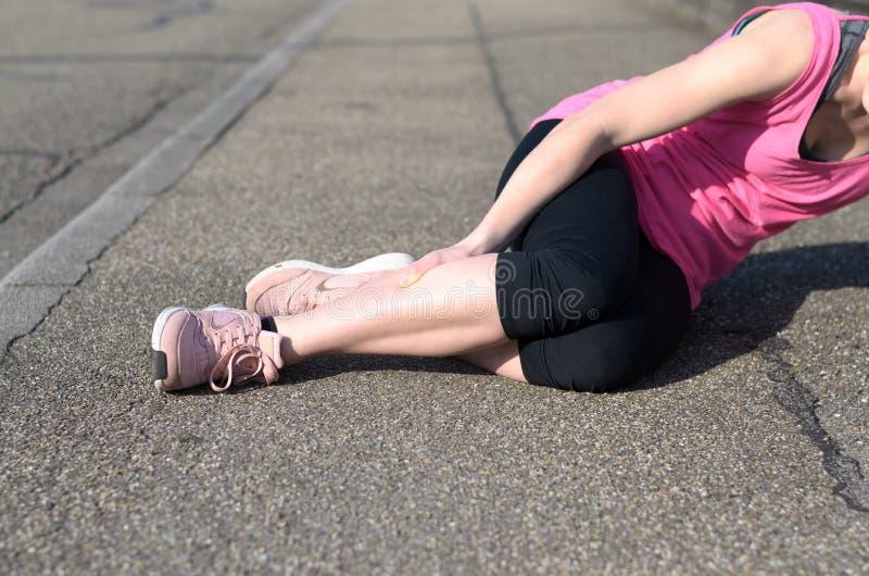 Żeńska atleta z łydkowymi drętwieniami fotografia stock