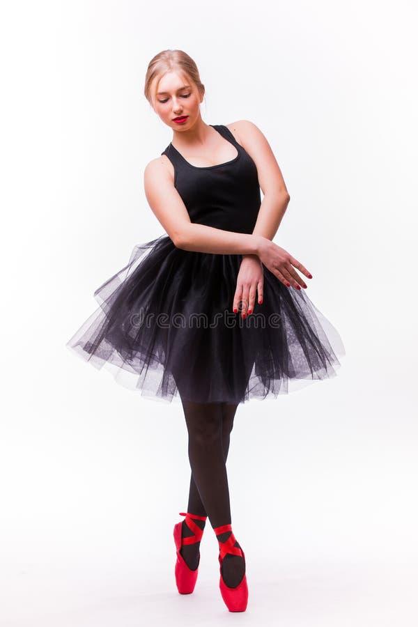 Żeńska balerina pozuje w białej spódniczce baletnicy i baletniczych butach na białym tle fotografia royalty free