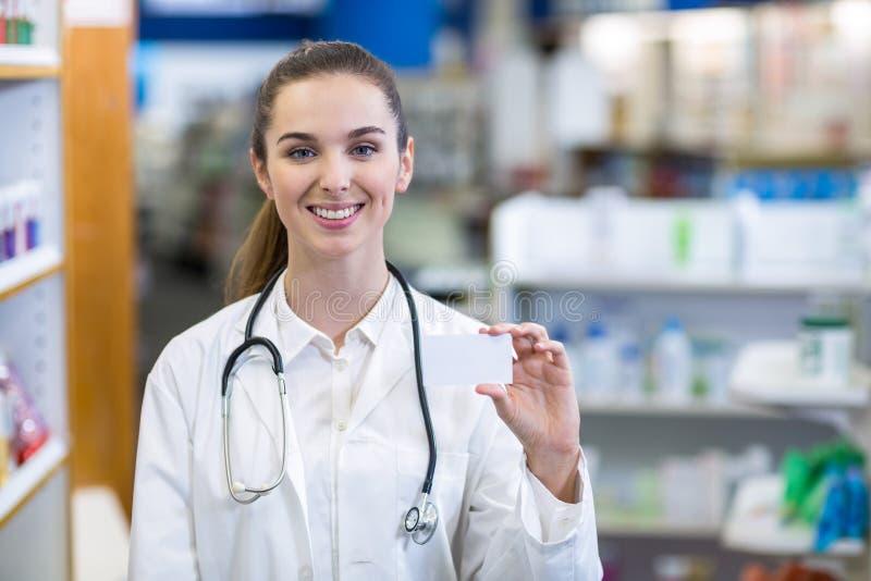 Żeńska farmaceuta trzyma pigułki pudełko w aptece zdjęcia royalty free
