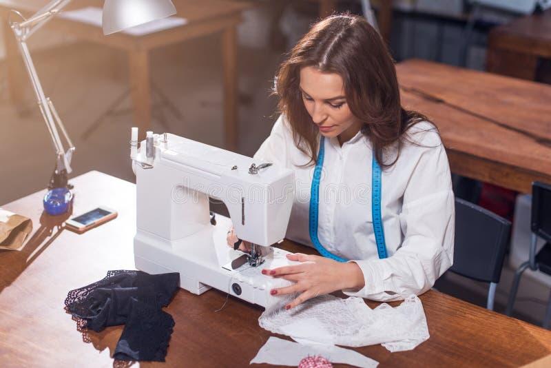Żeńska krawcowa pracuje z szwalną maszyną, zaszywanie tkaniny obsiadanie przy stołem w studiu zdjęcie royalty free
