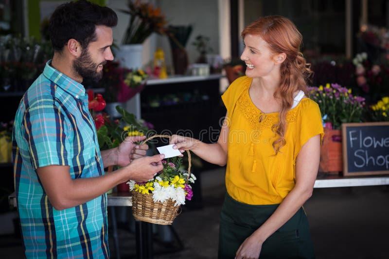 Żeńska kwiaciarnia daje klient odwiedzający karty i kwiatu kosz zdjęcia stock