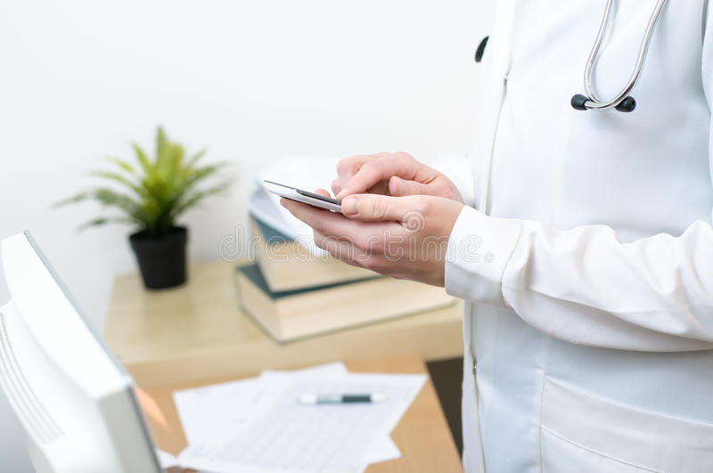 Żeńska lekarka texting na smartphone obrazy royalty free