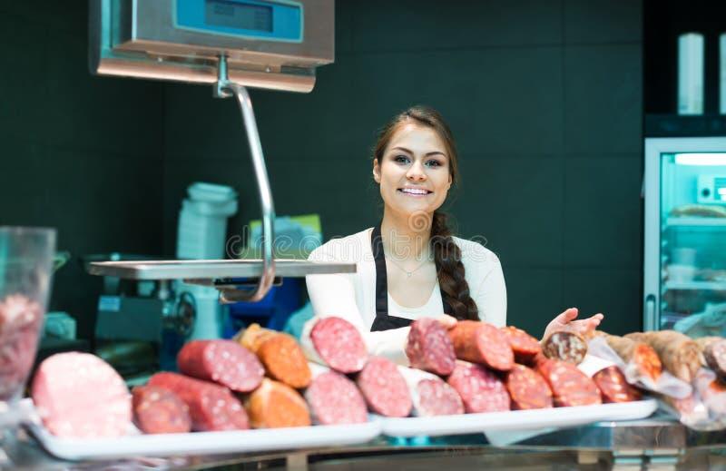 Żeńska masarka z wurst i bologna w mięsnym sklepu kontuarze obrazy royalty free