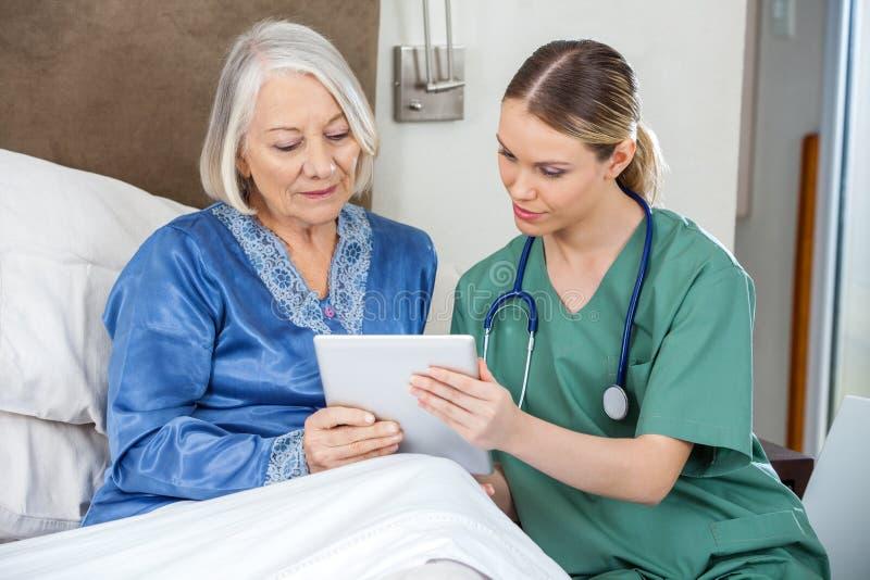 Żeńska pielęgniarka I senior kobieta Używa pastylka peceta zdjęcie stock