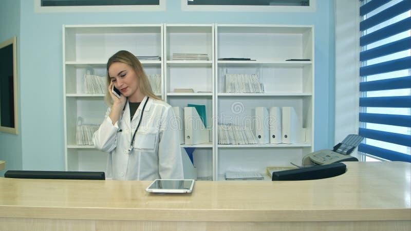 Żeńska pielęgniarka przy szpitalnymi recepcyjnymi odpowiadanie rozmowami telefonicza, planować cierpliwych spotkania i zdjęcia stock