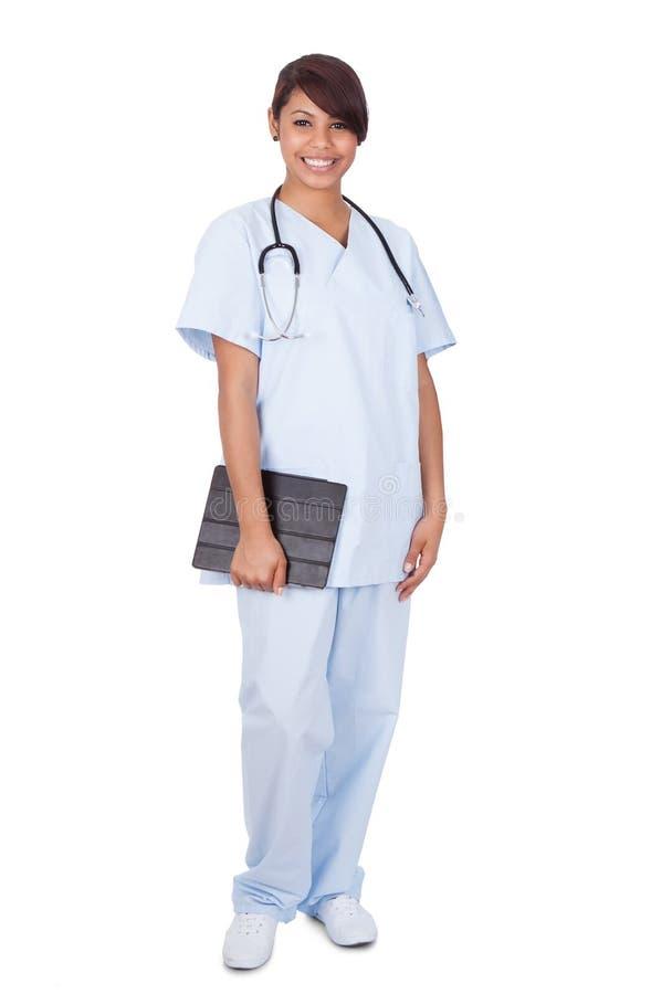 Żeńska pielęgniarka trzyma cyfrową pastylkę przeciw białemu tłu zdjęcia stock