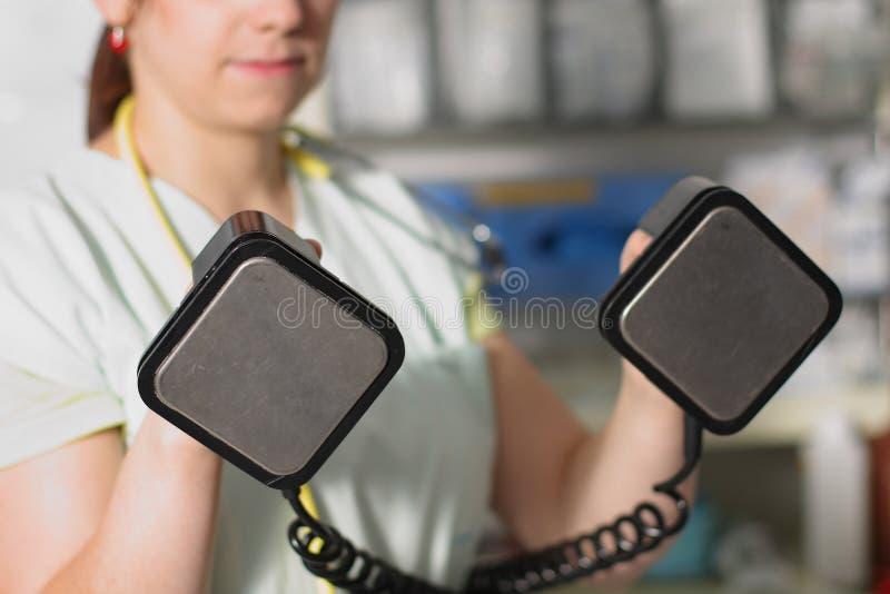 Żeńska pielęgniarka w ICU w zieleń mundurze z defibrillator fotografia stock