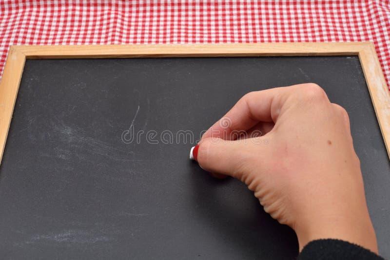 Żeńska ręka chce pisać coś na blackboard z kredą fotografia royalty free
