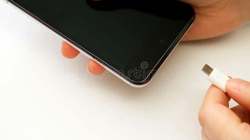 Żeńska ręka czopuje ładowarka telefonu komórkowego smartphone obrazy royalty free