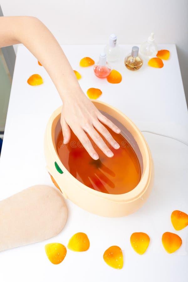 Żeńska ręka i pomarańczowy parafinowego wosku puchar. Kobieta w piękno salonie fotografia royalty free