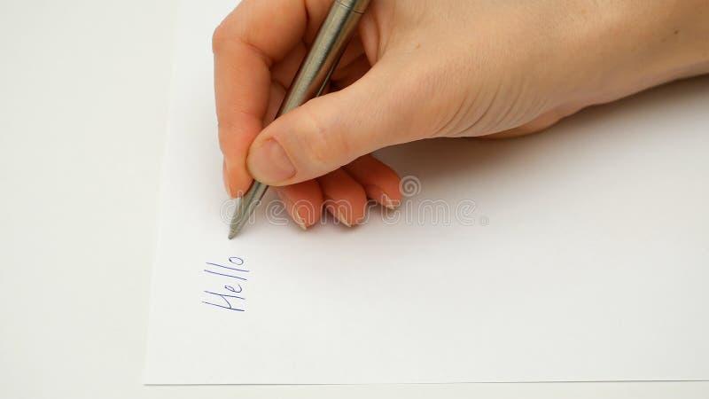 Żeńska ręka pisze na papierze Cześć zdjęcie royalty free