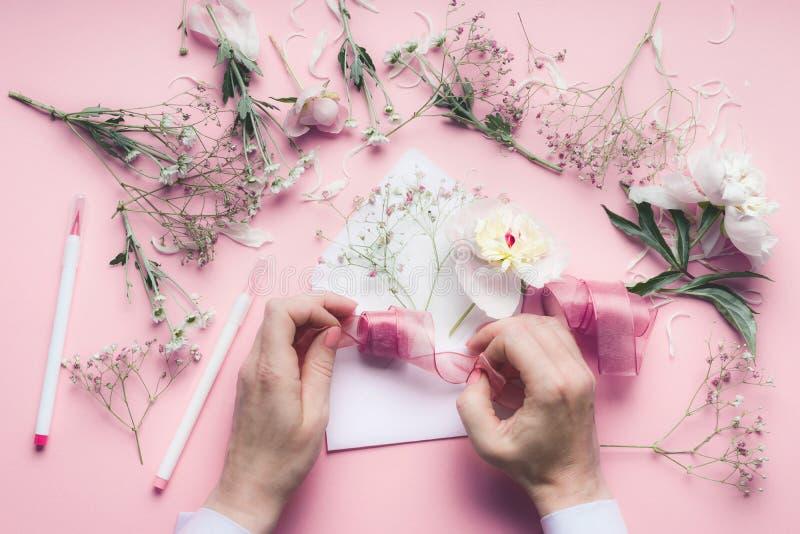 Żeńska ręka robi kartka z pozdrowieniami z kopertą z kwiatami Poślubiający, zaproszenie, walentynki, Matkuje ` s dnia pojęcie Mie obraz royalty free