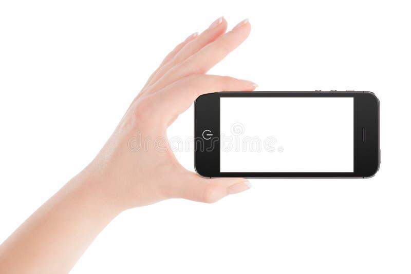 Żeńska ręka trzyma czarnego mądrze telefon w krajobrazowej orientaci zdjęcie royalty free