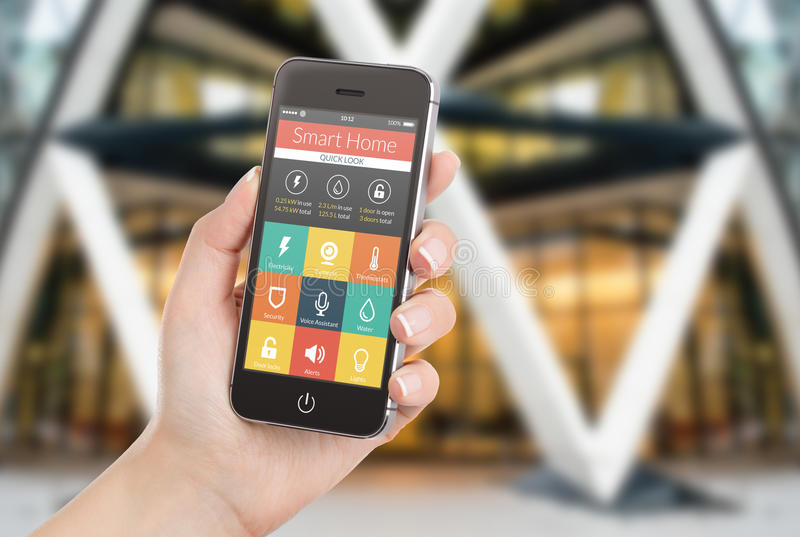 Żeńska ręka trzyma czarnego mądrze telefon z mądrze domowym applicatio zdjęcie royalty free
