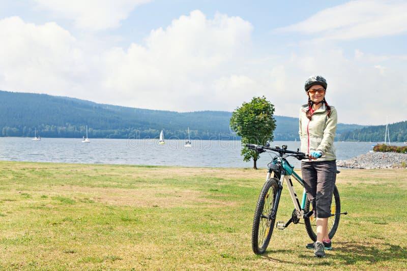 Żeńska turystyczna cyklista pozycja na brzeg jezioro na tle zdjęcia stock
