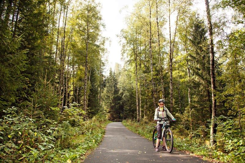 Żeńska turystyczna cyklista pozycja na drodze w lesie, patrzeje c fotografia royalty free