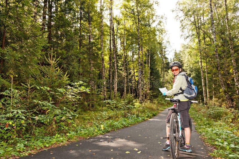 Żeńska turystyczna cyklista pozycja na drodze w lesie z mapą, lo obrazy royalty free